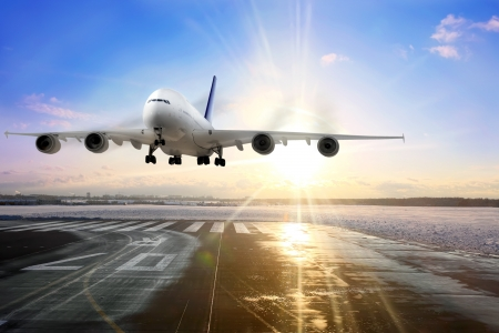 Passenger airplane landing on runway in airport. Evening