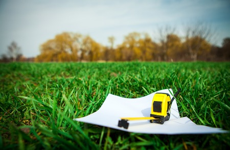Photo pour Papers and tape-measure with pencil on green grass in the park - image libre de droit