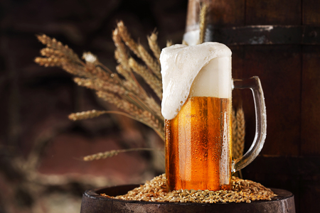 Foto de Mug of light beer pills with foam on a wooden barrel against stone wall. - Imagen libre de derechos