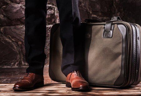 standing leg on the balck classikal trousers and brown oxfords.Chemodan with free space.suit case.concept waiting for something