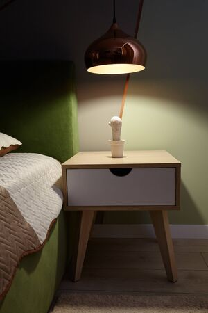 Photo for Bedroom lamp on a night table near sleeping bed.Dark room. - Royalty Free Image