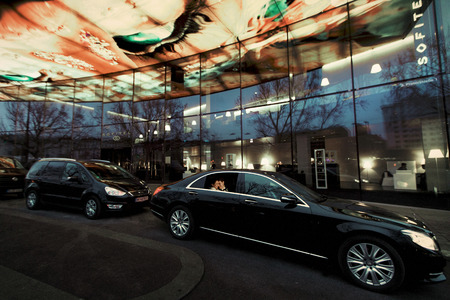 Black Mercedes with newlyweds inside stands on a glass parking