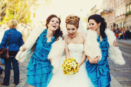 Bride full of energy dance with bridesmaids on the old street