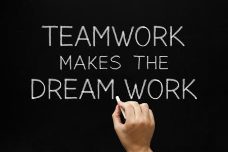 Hand writing Teamwork Makes The Dream Work with white chalk on a blackboard.