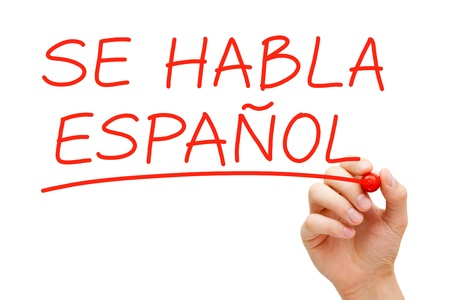 Hand writing Se Habla Espanol with red marker on transparent wipe board.