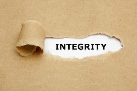 The word Integrity appearing behind torn brown paper.