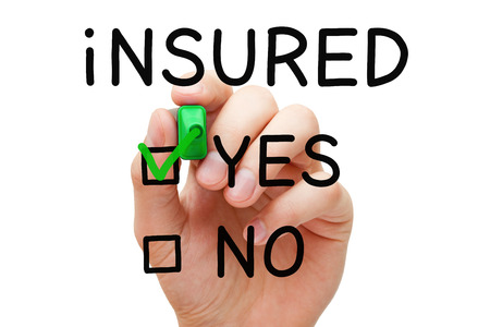 Hand putting check mark with green marker on Yes Insured.