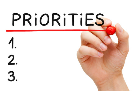 Hand writing Priorities list with marker isolated on white.
