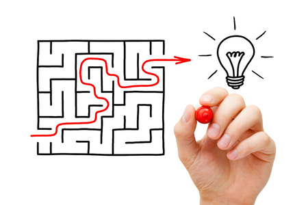 Hand drawing an red arrow going through a maze to a glowing light bulb. It's hard to find a great idea.