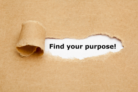 Find your purpose appearing behind torn brown paper.