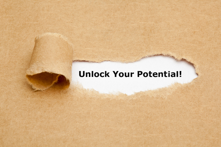 Foto de The text Unlock Your Potential appearing behind torn brown paper. - Imagen libre de derechos