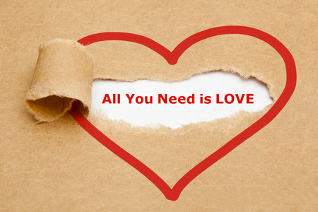 Photo for The text All You Need is Love appearing behind torn brown paper. - Royalty Free Image