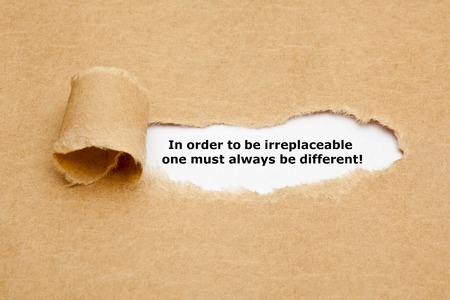 Photo pour The motivational quote In order to be irreplaceable one must always be different, appearing behind torn paper. - image libre de droit