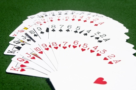 Complete deck of playing cards laid on the green playing table according to the suits.