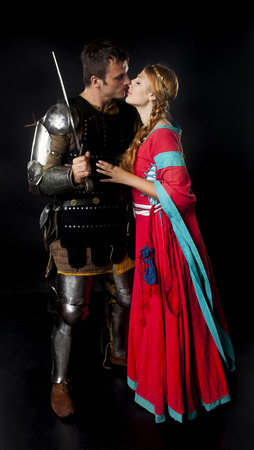 Studio shot of young couple dressed as Medieval knight and maiden kissing over black background