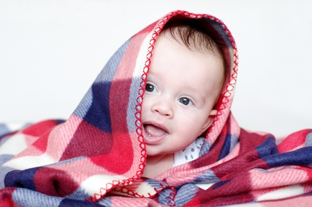Photo pour The four-months baby covered by a checkered plaid  - image libre de droit