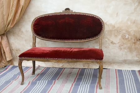 little red antique bench with curtains behind