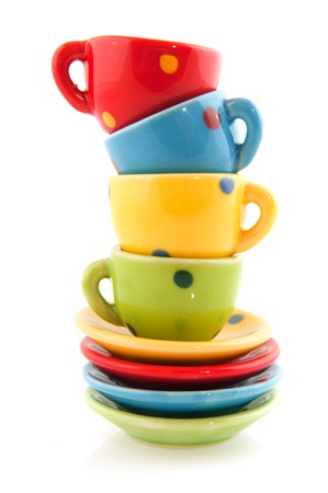 colorful stacked cups and saucers on white background