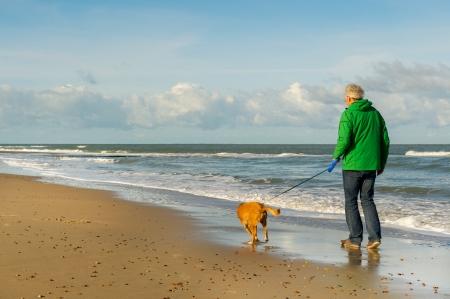 Foto de Senior man is walking the dog at the beach - Imagen libre de derechos