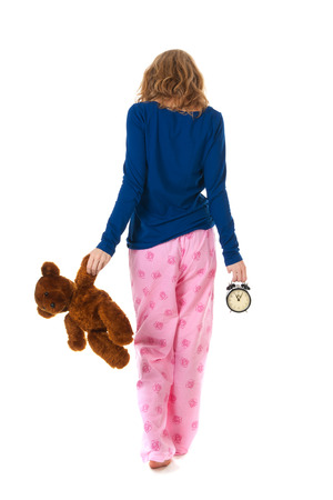 Young girl is going to bed with toy bear and alarm clock