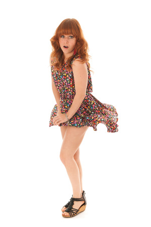 Attractive red haired girl standing in windy studio isolated over white background