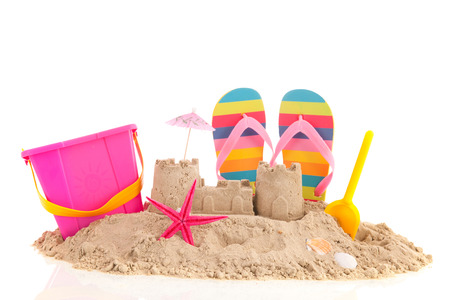 Foto de Sand castle andd toys at the beach isolated over white background - Imagen libre de derechos