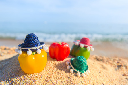 Colorful straw sombreros and healthy paprika at the beach