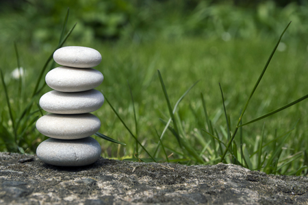 Harmony and balance, simple pebbles tower in the grass, simplicity, five stones