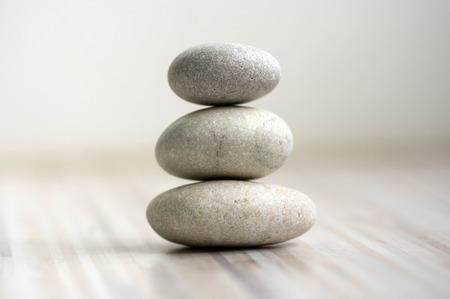Photo pour Harmony and balance, cairns, simple poise stones on wooden light white gray background, rock zen sculpture, five white pebbles, single tower, simplicity - image libre de droit