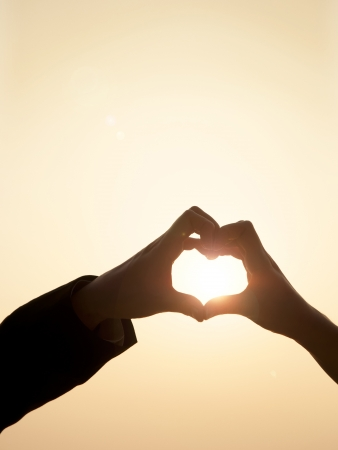 Shiloutte of two hands join to form a heart shape with sun beam inside the heart
