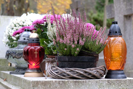 Photo pour Colorful glass candles between autumn flowers in flower pots on grave in cemetery on November day - image libre de droit