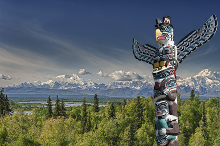 Isolated totem wood pole in mountain blue background