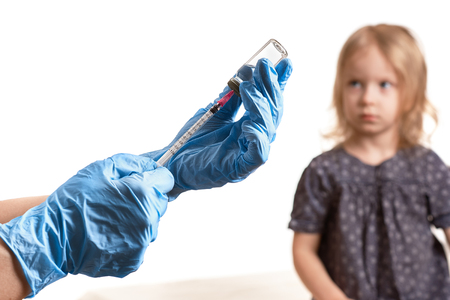 Healthcare concept : The doctor holding hypodermic syringe, Girl scared on background. Selective focus on a white background, free space for text.