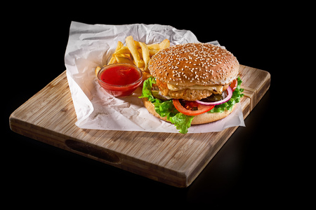 burger with french fries on wooden cutting board isolated on black background, close-up shot, selective focus.