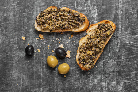 Foto per Bruschetta with green olives, anchovies,capers, selective focus, top view close-up - Immagine Royalty Free