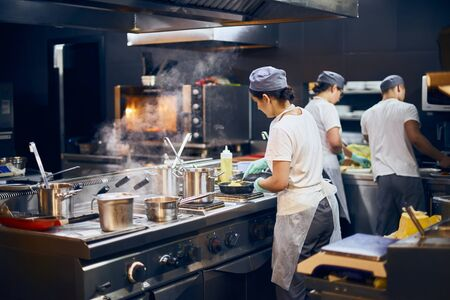 Photo for the team of cooks backs in the work in the modern kitchen, the workflow of the restaurant in the kitchen. Copy space for text - Royalty Free Image