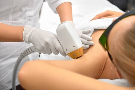 Photo pour Hair removal cosmetology procedure from a therapist at cosmetic beauty spa clinic. Laser epilation underarm. Cosmetology and SPA concept. - image libre de droit