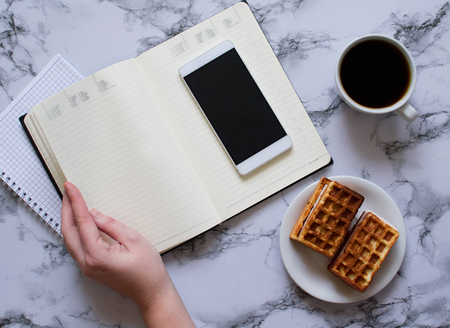 Woman are planning the day, coffee, waffles, marble background