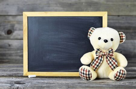 Photo pour Teddy bear with blank blackboard on wooden background - image libre de droit
