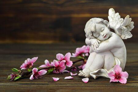 Foto de Guardian angel and spring flowers on wooden background - Imagen libre de derechos