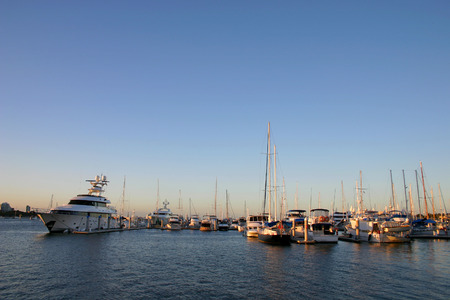 Yachts cruisers and a superyacht all moored at marina.
