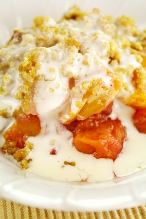 Seasonal fruit crumble dessert with cream ready to serve.