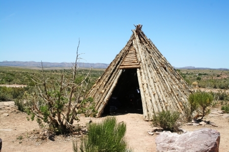 A native American Indian teepee made of wood sitting in the desert.