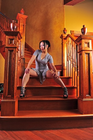 A seductive beautiful young Asian woman high heels and a short dress sits on the stairs.