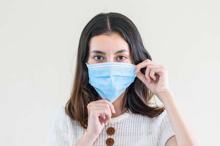 Foto de young  beautiful asian woman showing how to wear a medical mask or  showing how to correctly wear hygiene surgical mask step by step on white background - Imagen libre de derechos