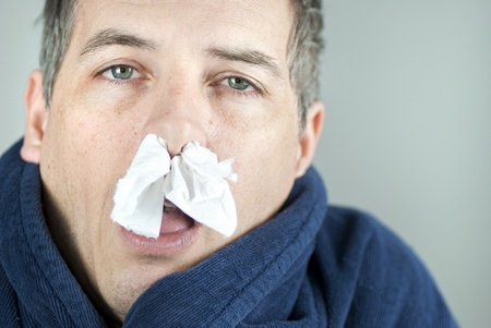 Close-up of a man with tissue in his nose.