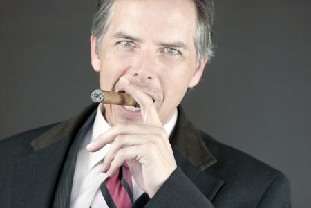 Close-up of a confident businessman smoking a cigar.