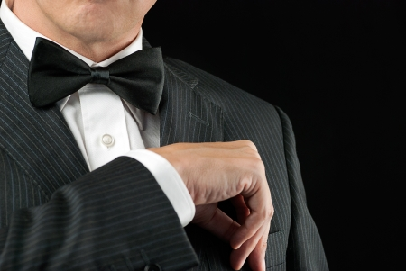 Close-up of a man in a tux tucking in his pocket square