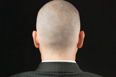 Close-up of a bald suited man, shot from behind