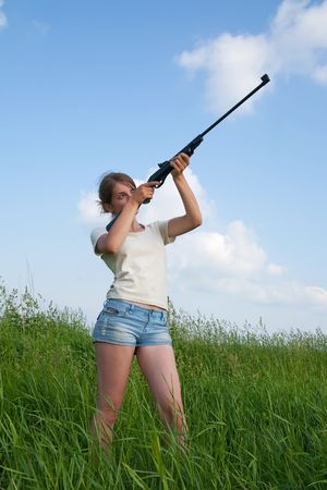 young woman aiming a pneumatic air rifle